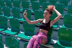 一个人美丽,微笑,性感的非裔美国人的女孩在电话为照相坐在行的一把绿色椅子为 免版税库存图片