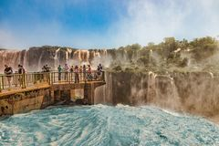 一个人行桥的人们在巴西边的伊瓜苏瀑布中间 图库摄影
