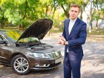 一个人表示,他是晚身分在路的一辆残破的汽车附近 外面 免版税库存图片