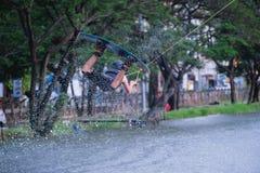 一个人被实践跳跃他的在空气和水飞溅的wakeboard在湖 在极端公园的水上运动 免版税库存照片