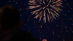 一个人观看的爆炸的烟花的剪影以纪念假日 庆祝的致敬 影视素材