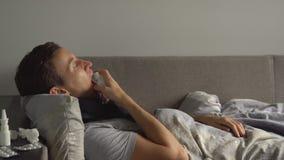 一个人说谎的病残在他的疗程旁边的床上在他的家和洒在她的喉头的喉头浪花 免版税库存图片