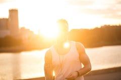 一个人赛跑者的运动员足迹连续剪影在日落sunri的 库存照片