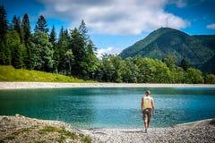 一个人走往奥地利的阿尔卑斯山的湖Speicherteich 库存照片