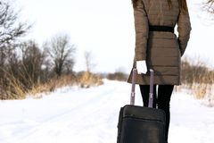 一个人走路与旅行袋子 在铁路路附近的城市发光雪星期日对冬天木头 库存照片