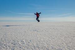 一个人跳进一个巨大的白色草甸 库存图片