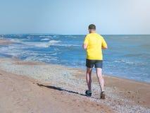 一个人通过早晨跑海滩在阳光下 免版税图库摄影