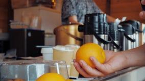 一个人采取从咖啡馆柜台的一个桔子并且投掷它入空气 股票视频