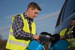 一个人重新装满他的从蓝色气体罐的汽车在街道上 免版税图库摄影