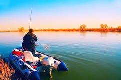 一个人钓鱼与在河的一条可膨胀的小船 免版税库存图片