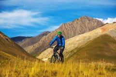 一个人骑在山的一辆自行车 在山吉尔吉斯斯坦的秋天 免版税图库摄影