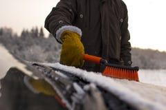 一个人,从雪清洗汽车 免版税库存图片