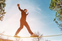 一个人,变老与胡子和佩带的太阳镜,在一slackline露天平衡在两棵树之间在日落 库存照片
