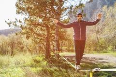 一个人,变老与胡子和佩带的太阳镜,在一slackline露天平衡在两棵树之间在日落 免版税图库摄影