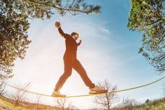 一个人,变老与胡子和佩带的太阳镜,在一slackline露天平衡在两棵树之间在日落 免版税库存图片