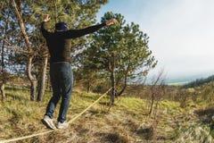 一个人,变老与胡子和佩带的太阳镜,在一slackline露天平衡在两棵树之间在日落 图库摄影