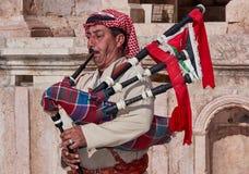 一个人,打扮在一套全国服装,当他的眼睛闭上,在古老北罗马剧院弹风笛 库存照片