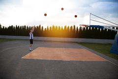 一个人,站立高,准备射击篮球,在公园 库存照片
