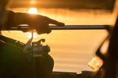 一个人从在日落的一条小船钓鱼 手和标尺特写镜头  库存图片