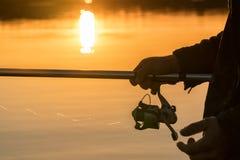 一个人从在日落的一条小船钓鱼 手和标尺特写镜头  免版税库存照片