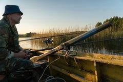 一个人从在日落的一条小船钓鱼 库存图片