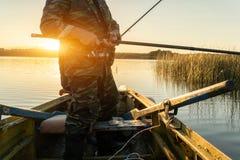 一个人从在日落的一条小船钓鱼 图库摄影