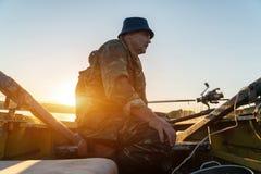 一个人从在日落的一条小船钓鱼 免版税库存图片