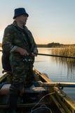 一个人从在日落的一条小船钓鱼 免版税库存照片