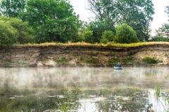 一个人从在河的一条小船钓鱼 免版税图库摄影