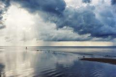 一个人从太阳的光芒的背景的海出来 库存图片