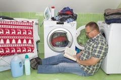 一个人洗涤在洗衣机的衣裳 家事人 帮助他的妻子的人,当洗涤衣裳时 免版税库存照片
