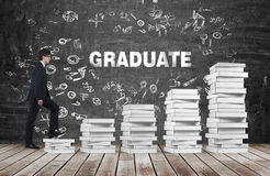 一个人去用完由白皮书制成的台阶 词毕业生是在黑黑板 免版税图库摄影