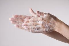 一个人洗他的手用肥皂和水 免版税库存图片