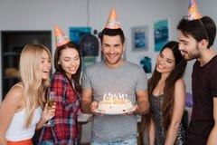 一个人` s生日和他的朋友祝贺他 客人在生日男孩附近站立 人举行a 免版税库存照片
