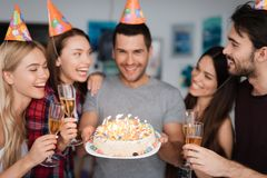 一个人` s生日和他的朋友祝贺他 客人在生日男孩附近站立 人举行a 免版税图库摄影