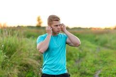 一个人atlen在公园礼服的立场耳机,确信的神色 夏天生活方式,刺激是强的 羊毛衫 免版税库存照片