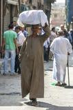 一个人carrys物品装载通过可汗el Khal'ili义卖市场在开罗,埃及 免版税图库摄影
