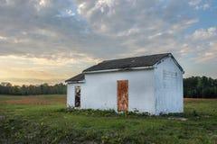 一个任意领域的被放弃的房子在日落前面 库存图片