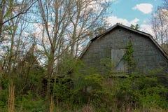 一个任意领域的被放弃的房子在日落前面 图库摄影