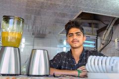 一个伊朗男孩在东部义卖市场卖汁液 库存照片