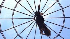 一个优美的女孩在空气杂技演员的一个圆环坐并且延长她的胳膊,慢动作 股票视频