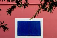 一个传统建筑的桃红色淡色墙壁与蓝色木风的 库存照片