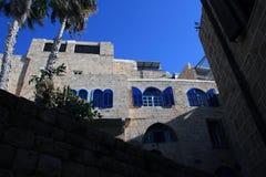 一个传统房子的看法 有蓝色快门的石墙 免版税图库摄影