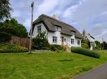 一个传统英国村庄和茅屋顶的看法有一个很好被绘的草坪区域的 免版税库存图片