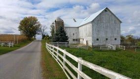 一个传统门诺派中的严紧派的谷仓和一个白色尖桩篱栅在俄亥俄,美国 库存图片