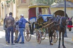 一个传统马小室所有者谈话与游人 免版税库存图片