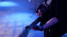 一个低音吉他弹奏者的美丽的特写镜头摇滚乐音乐会的 非常美好的光 在低音演奏员的手套的手上 股票视频