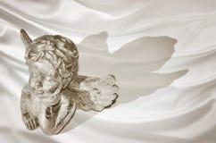 一个作的天使的小雕象在丝绸背景的 图库摄影