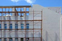 一个使用脚手架的大厦和膏药的建筑与外部保温的 免版税库存照片