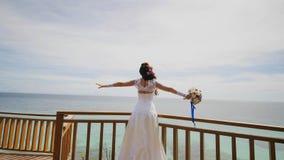 一个使目炫的新娘享受从俯视海洋和礁石的阳台的高度的幸福 爱飞行  异乎寻常 库存图片